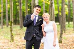 April Fools ' dag Gifta sig par som poserar med pinnekanter, maskering Royaltyfri Foto