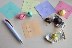 April fools day prank. Wrapping hazelnut in candy wrappers on wooden table. Joke with food.  royalty free stock photo