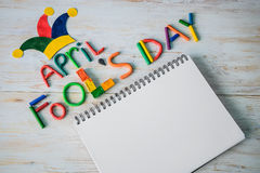 April Fools` Day text made with plasticine and free space in note. April Fools` Day text made with plasticine and free sapce on note on white wooden background Royalty Free Stock Image