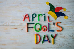 April Fools` Day text made with plasticine. On white wooden background Stock Photo