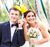 April Fools' Day. Wedding couple posing with crown, mask. Stock Photo