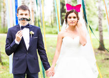 April Fools' Day. Wedding couple posing with mask. April Fools' Day. Wedding couple posing with crown, mask royalty free stock photos