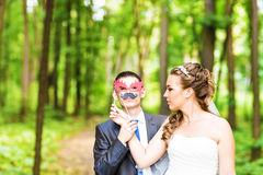 April Fools' Day. Wedding couple posing with stick lips, mask. Stock Photos