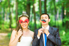 April Fools' Day. Wedding couple posing with stick lips, mask. Royalty Free Stock Images