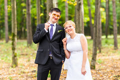 April Fools' Day. Wedding couple posing with stick lips, mask. April Fools' Day. Wedding couple posing with stick lips, mask royalty free stock photos