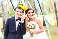 April Fools-' Tag Hochzeitspaare, die mit Krone, Maske aufwerfen Stockfoto