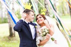 April Fools-' Tag Hochzeitspaare, die mit Krone, Maske aufwerfen Lizenzfreie Stockfotos