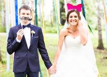 April Fools-' Tag Hochzeitspaare, die mit Maske aufwerfen Lizenzfreies Stockfoto