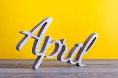 April - geschnitzter Text von hölzernem am hellgelben Hintergrund Zweiter Frühlingsmonat Stockfotografie