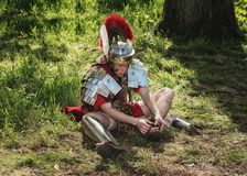 Roman centurion put on his sandals during the Elf Fantasy Fair. April  19, 2014, Haarzuilens, The Netherlands: Roman centurion put on his sandals during the Elf Royalty Free Stock Photo