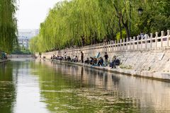 April 2015 - Jinan, China - local people fishing in the City moat of Jinan, China. April 2015 - Jinan, China - local people fishing in the City moat running stock photography