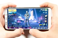 April, 2019. Kramatorsk, Ukraine. The gameplay of the game PUBG G Mobile on a white smartphone. In hand stock images