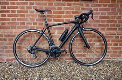 28. April 2019 - London, Vereinigtes Königreich: Stilvolle schwarze Fahrradstellung gegen verwitterte Backsteinmauer lizenzfreies stockfoto