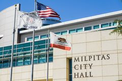 April 30, 2017 Milpitas/CA/USA - The City Hall Building on a sunny spring day; the City of Milpitas, USA and the State of. California flags blowing in the wind stock image