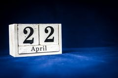 April 22nd, Twenty-second of April, Day 22 of month April - rustic wooden white calendar blocks on dark blue background with empty