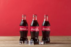 Coca-Cola bottle with ice cubes on wooden background. stock photo