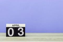 April 3rd Dag 3 av månaden, kalender på trätabellen och lilabakgrund Vårtid, tömmer utrymme för text Royaltyfri Fotografi