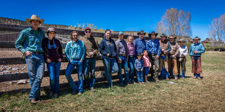 APRIL 22, 2017, RIDGWAY COLORADO: Cowboys and Cowgirls pose against fence at Centennial Ranch, Ridgway, Colorado- a cattle ranch o Royalty Free Stock Photos