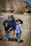 22. APRIL 2017 RIDGWAY COLORADO: Junger Cowboy und Vater brandmarken Vieh auf hundertjähriger Ranch, Ridgway, Colorado - eine Ran lizenzfreie stockbilder