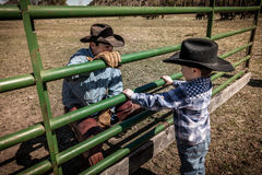 APRIL 22, 2017, RIDGWAY COLORADO: Young cowboy watches older Cowboys brand cattle on Centennial Ranch, Ridgway, Colorado - a ranch. With Angus/Hereford cross stock photos