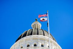 April 14, 2018 Sacramento / CA / USA - The US and the California state flag waving in the wind in front of the dome of the. California State Capitol stock photography