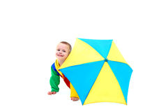 April Showers. Little boy hides behind a colorful umbrella waiting for April showers to be over.  He is wearing a colorful raincoat and behind a yellow and blue Royalty Free Stock Photos