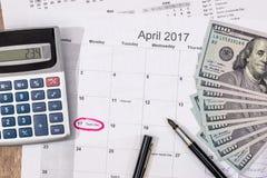 15 april, skattdag på kalender med den röda markörpennan med dollarsedeln Arkivfoto