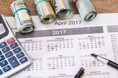 15 april, skattdag på kalender med den röda markörpennan med dollarsedeln Arkivfoton