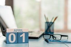 April 1st dag 1 av månaden, kalender på bakgrund för affärskontor, arbetsplats med bärbara datorn och exponeringsglas Vårtid som  Arkivfoto
