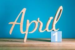 April 1st dag 1 av månaden, kalender på trätabellen och gräsplanbakgrund Vårtid, tömmer utrymme för text Arkivfoton
