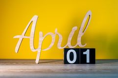 April 1st dag 1 av månaden, kalender på trätabellen och gräsplanbakgrund Vårtid, tömmer utrymme för text Royaltyfri Bild
