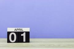 April 1st dag 1 av månaden, kalender på trätabellen och lilabakgrund Vårtid, tömmer utrymme för text Royaltyfri Foto