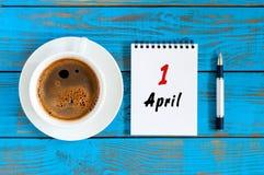 April 1st dag 1 av månaden, lösblads- kalender med morgonkaffekoppen, på arbetsplatsen Vårtid, bästa sikt Royaltyfria Bilder