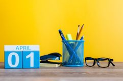 April 1st. Day 1 of april month, calendar on table with yellow background and office or school supplies. Spring time.  Royalty Free Stock Photo