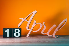 April 18st. Day 18 of month, daily wooden calendar on table with orange background. Spring time concept Stock Images