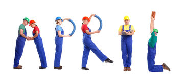 April staff. Group of young people wearing different color uniforms and hard hats forming April word - isolated on white background - calendar concept Royalty Free Stock Photography