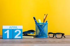 12. April Tag 12 des Monats, Kalender auf Geschäftsbürotisch, Arbeitsplatz mit gelbem Hintergrund Frühlingszeit… Rosenblätter, na Lizenzfreie Stockfotografie