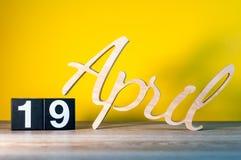 19. April Tag 19 des Monats, Kalender auf Holztisch und Grünhintergrund Frühlingszeit, leerer Raum für Text lizenzfreies stockfoto