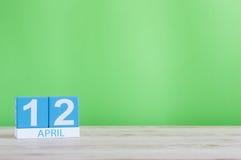 12. April Tag 12 des Monats, Kalender auf Holztisch und Grünhintergrund Frühlingszeit, leerer Raum für Text Lizenzfreies Stockbild