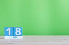 18. April Tag 18 des Monats, Kalender auf Holztisch und Grünhintergrund Frühlingszeit, leerer Raum für Text Lizenzfreies Stockbild