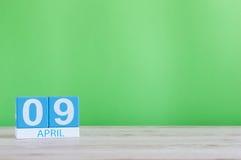 9. April Tag 9 des Monats, Kalender auf Holztisch und Grünhintergrund Frühlingszeit, leerer Raum für Text Lizenzfreie Stockbilder
