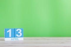 13. April Tag 13 des Monats, Kalender auf Holztisch und Grünhintergrund Frühlingszeit, leerer Raum für Text Lizenzfreie Stockfotos