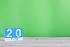 20. April Tag 20 des Monats, Kalender auf Holztisch und Grünhintergrund Frühlingszeit, leerer Raum für Text Lizenzfreies Stockbild