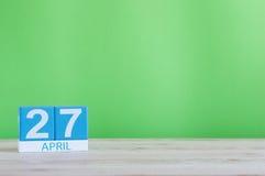 27. April Tag 27 des Monats, Kalender auf Holztisch und Grünhintergrund Frühlingszeit, leerer Raum für Text Lizenzfreie Stockfotos