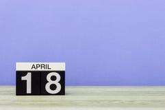 18. April Tag 18 des Monats, Kalender auf Holztisch und Purpurhintergrund Frühlingszeit, leerer Raum für Text Lizenzfreie Stockfotografie