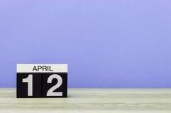 12. April Tag 12 des Monats, Kalender auf Holztisch und Purpurhintergrund Frühlingszeit, leerer Raum für Text Lizenzfreie Stockfotografie