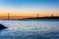 April 25th Bridge and Christ the King statue in Lisbon Portugal at sunrise. April 25th Bridge, Tagus River and Christ the King statue in Lisbon Portugal at Royalty Free Stock Photo