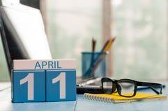 April 11th Dag 11 av månaden, kalender på bakgrund för affärskontor, arbetsplats med bärbara datorn och exponeringsglas Fjädra de Arkivfoto