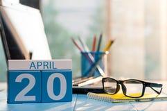 April 20th Dag 20 av månaden, kalender på bakgrund för affärskontor, arbetsplats med bärbara datorn och exponeringsglas Fjädra de Royaltyfri Foto