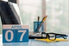 April 7th Dag 7 av månaden, kalender på bakgrund för affärskontor, arbetsplats med bärbara datorn och exponeringsglas Vårtid som  Royaltyfri Foto
